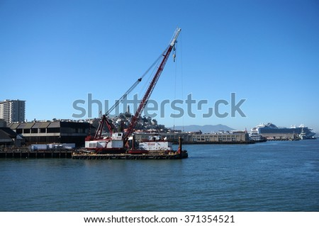SAN FRANCISCO - OCTOBER 11:  Crane on barge does Pier repair work with Coit Tower on top Telegraph hill and Cruise ship in the distance in San Francisco, California.  October 11, 2015. - stock photo