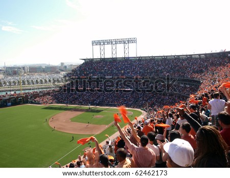 SAN FRANCISCO - OCTOBER 2: Padres vs. Giants: Fans wave orange towels to celebrate giants hit on offense.  taken on October 2 2010 at Att Park in San Francisco California. - stock photo