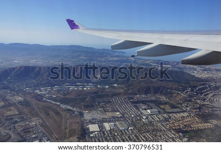 SAN FRANCISCO - OCTOBER 13: Wing of Hawaiian Airlines plane flying in the air above city of San Francisco and ocean on October 13, 2015. - stock photo