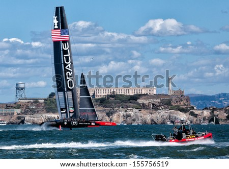 SAN FRANCISCO-SEPT 25: Oracle Team USA approaches Alcatraz Island during the final race of America's Cup with New Zealand on Sept. 25, 2013 in San Francisco. USA won the race in a historic comeback. - stock photo