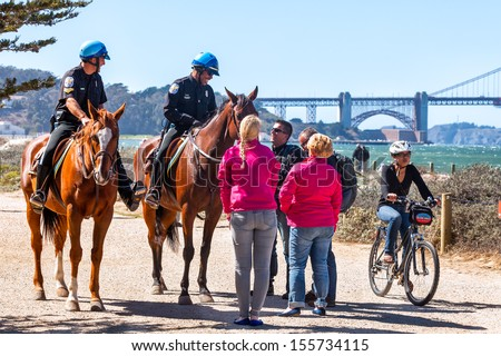 SAN FRANCISCO-SEPT 25: US Park Police officers greet visitors on Sept. 25, 2013 in San Francisco. The federal horse-mounted patrol operates only in parks in Washington DC, New York and San Francisco. - stock photo