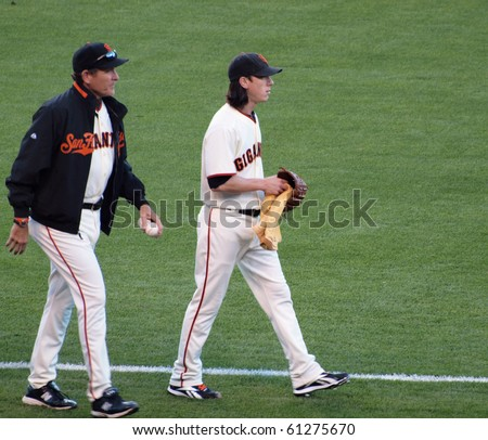 SAN FRANCISCO - SEPTEMBER 18: Brewers vs. Giants: Cy Young award winner pitcher Tim Lincecum walks towards the mound with pitching coach.  September 18 2010 ATT Park San Francisco California. - stock photo