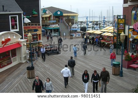 SAN FRANCISCO - SEPTEMBER 20: Tourists enjoy famous Fisherman's Wharf on September 20, 2007 in San Francisco, California. The wharf was originally settled by immigrant fisherman. - stock photo