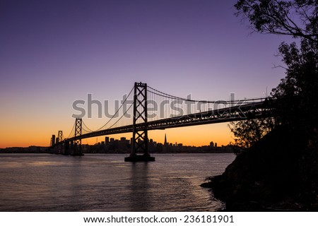 San Francisco skyline and Bay Bridge at sunset, California USA - stock photo