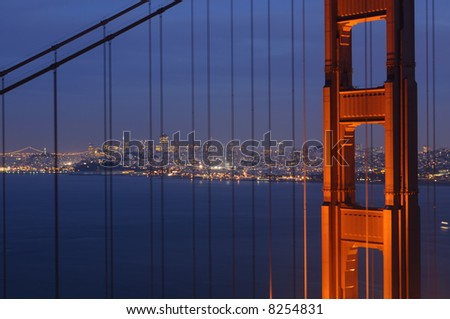 San Francisco skyline and Bay Bridge illumination framed by glowing Golden Gate pillar and steel cables.