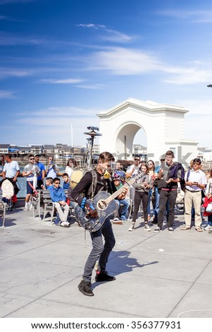 San-Francisco-United States,July 13,2014: Positive Caucasian Male Multiplayer Musician Performing Outdoors on San-Francisco Pier on July 13, 2014 in San-Francisco, California, United States of America - stock photo