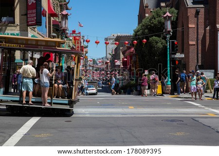 SAN FRANCISCO, USA - JUNE 29:  Famous tram filled with people, hanging out of the vehicle, on the steep streets at the corner of Chinatown, downtown on June 29, 2013 in San Francisco, USA - stock photo