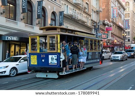 SAN FRANCISCO, USA - JUNE 29:  Famous tram stuffed with people, even hanging out of the vehicle, on the steep streets in Powel Street downtown San Francisco on June 29, 2013 in San Francisco, USA - stock photo