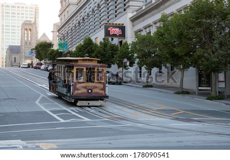 SAN FRANCISCO, USA - JUNE 29:  Famous tram stuffed with people, even hanging out of the vehicle, on the steep  California Street in downtown San Francisco on June 29, 2013 in San Francisco, USA - stock photo