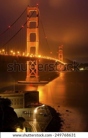 SAN FRANCISCO, USA - MARCH 1 2014: The famous Golden Gate Bridge in California,United States of America. A long exposure of Fort Point, the bay and the illuminated red suspended bridge at night. - stock photo