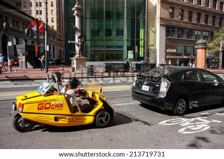 SAN FRANCISCO, USA - OCT 2, 2011: Tourists make GPS-guided tour on special equipped three-wheel story telling car on Oct 2, 2011 in San Francisco, USA. Service was launched in 2004   - stock photo