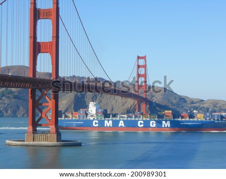 SAN FRANCISCO, USA - OCTOBER 18, 2013: A merchant ship passing under the Golden Gate suspension bridge spanning the Golden Gate strait channel between San Francisco Bay and the Pacific Ocean