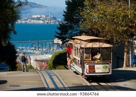 SAN FRANCISCO, USA - SEPT. 21:  Tourists ride the cable car on a sunny day at the top of Hyde Street overlooking Alcatraz in San Francisco September 21, 2011 in San Francisco, USA - stock photo