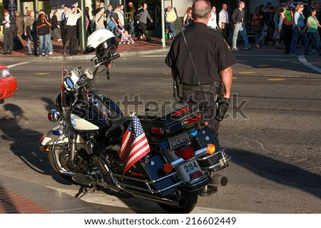 SAN FRANCISCO, USA - SEPT 24, 2008: US policeman patrols city street crowded by attendees of Oracle OpenWorld conference on Sept 24, 2008 in San Francisco, USA. 40,000 specialists visited this forum  - stock photo
