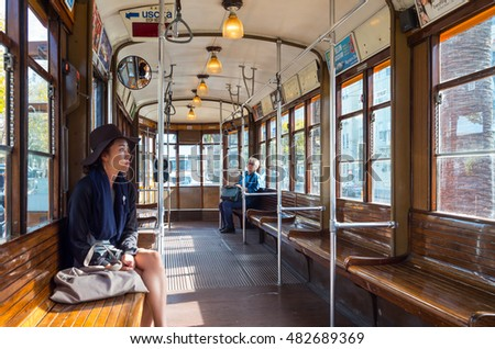 San Francisco, USA - September 26, 2015:  A young tourist with an old lady on background in a vintage tram running in the city center
