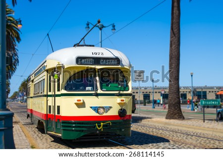 San Francisco vintage f- streetcar, train, tram or muni cable trolley car traveling down the Embarcadero on a sunny day.  Originally a Mexico City car built in 1946 trolley.  Tribute livery. - stock photo