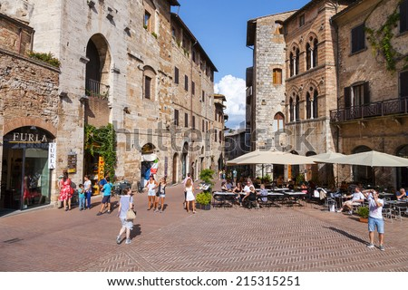 SAN GIMIGNANO, ITALY - 27th of August 2014: Tourists walk in San Gimignano, Italy. The Historic Centre of San Gimignano is a UNESCO World Heritage Site on 27th of August 2014 in SAN GIMIGNANO, ITALY  - stock photo