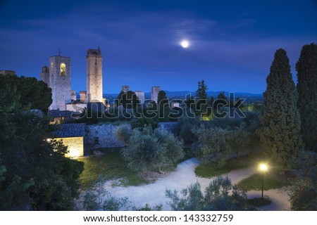San Gimignano on night, medieval town landmark. Moon light on towers and park with cypress and olive trees. Tuscany, Italy, Europe. - stock photo