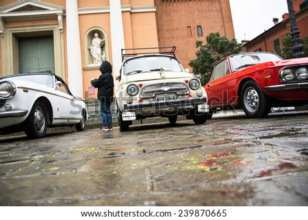 SAN GIOVANNI IN PERSICETO,BOLOGNA,ITALY-MARCH 1,2014:meeting of classic cars in the square of city in a rainy day