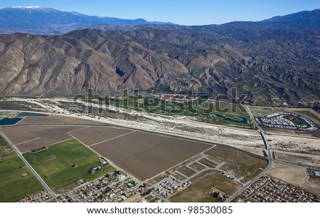 San Jacinto, California area with golf course along the river bed and snow capped Mount San Gorgonio in the distance - stock photo