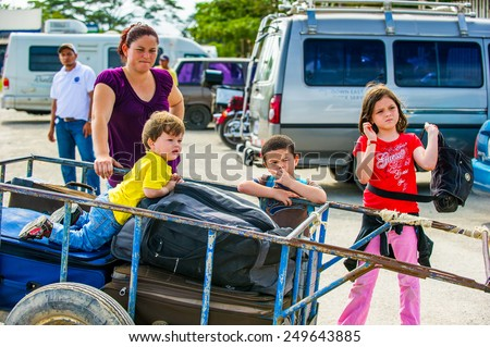 SAN JOSE, COSTA RICA - JAN 6, 2012: Unidentified Costa Rican children in a carriage with luggage. 65.8% of Costa Rican people belong to the White (Castizo) ethnic group