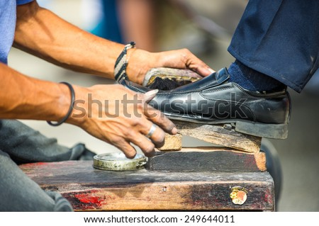 SAN JOSE, COSTA RICA - JAN 6, 2012: Unidentified Costa Rican man cleans shoes to the other man. 65.8% of Costa Rican people belong to the White (Castizo) ethnic group