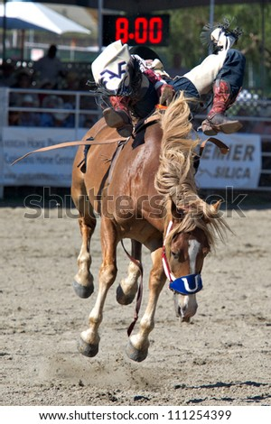 SAN JUAN CAPISTRANO, CA - AUGUST 25: unidentified cowboy competes in the bareback riding event at the PRCA Rancho Mission Viejo rodeo in San Juan Capistrano, CA on August 25, 2012. - stock photo