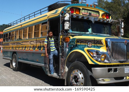 SAN JUAN LA LAGUNA, GUATEMALA -  NOVEMBER 27: Close-up of a colored bus in the town center with a man on the running board , on November 27, 2013, in San Juan La Laguna, Guatemala.  - stock photo
