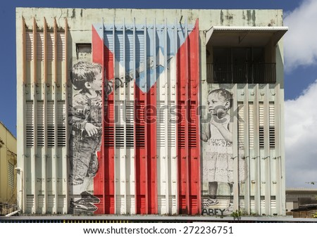 SAN JUAN, PUERTO RICO - MARCH 13, 2015: Graffiti in Tras Talleres neighborhood. Large image of a Caucasian boy and an African girl adding the star to the Puerto Rico Flag. Painted on warehouse wall. - stock photo