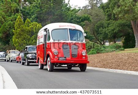 SAN MARINO/CALIFORNIA - JUNE 12, 2016: A classic Metro truck cruises down a narrow road followed by a fleet of vintage cars in San Marino, California USA - stock photo