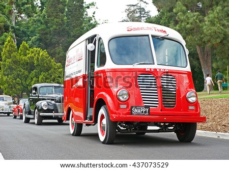 SAN MARINO/CALIFORNIA - JUNE 12, 2016: A classic Metro truck cruises down a narrow road followed by several vintage cars in San Marino, California USA - stock photo