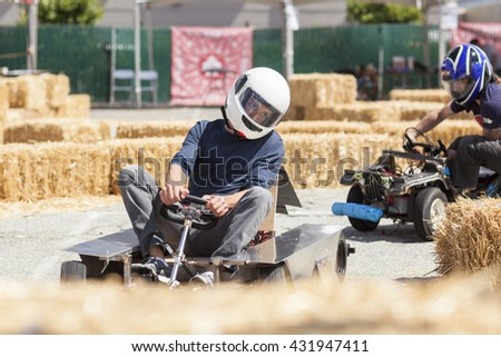 SAN MATEO, CA May 20 2016 - A driver looks ahead around a curve during a power wheels race at the 11th Annual Bay Area Maker Faire at the San Mateo County Event Center. - stock photo