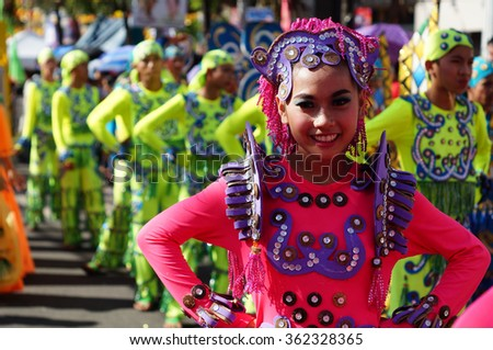 SAN PABLO CITY, LAGUNA, PHILIPPINES - JANUARY 13, 2016: a group of carnival dancers in various costumes dance along the road during the 21st annual coconut festival cultural celebration. - stock photo