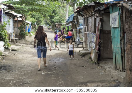 SAN PABLO CITY, LAGUNA, PHILIPPINES - JANUARY 9, 2016: Fearless Young lady walking along a slum rough road street unaccompanied - stock photo