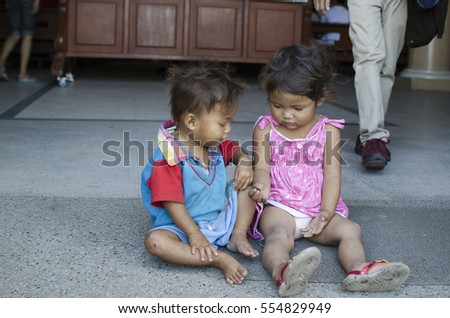 SAN PABLO CITY, LAGUNA, PHILIPPINES - JANUARY 6, 2017: homeless beggar's children boy and girl, seated, take care of each other at church yard