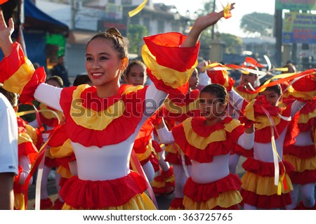 SAN PABLO CITY, LAGUNA, PHILIPPINES - JANUARY 17, 2016:  School girls parade and dance on the street in colorful costumes, carrying Infant Jesus icon to celebrate the annual sinulog festival - stock photo