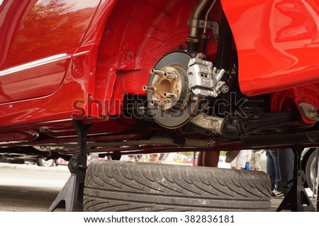 San Pablo City, Laguna, Philippines - September 12, 2015: Wheel of a red car tire removed showing disk brake - stock photo