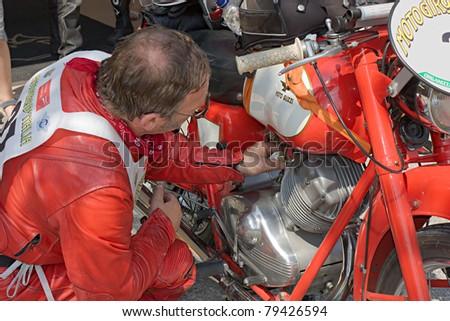 "SAN PANCRAZIO, RAVENNA, ITALY - JUNE 2: Sorbi Joe checks his bike Moto Guzzi Lodola S. (1957) at  pause of ""Motogiro d' Italia"", race for old motorcycles on June 2011 in San Pancrazio, Ravenna, Italy - stock photo"