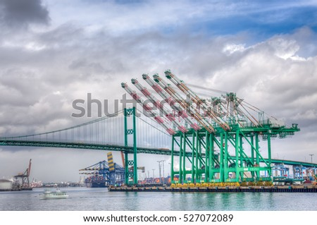 SAN PEDRO, CA/USA - JANUARY 18, 2016: Evergreen Marine Corporation Container Cranes with the Vincent Thomas Bridge in background at Port of Los Angeles.