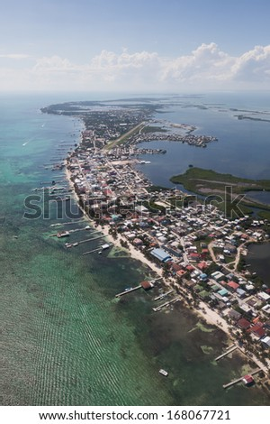 San Pedro town on Ambergris Caye, Belize in the Caribbean as seen from the air with calm waters provided by the protective offshore coral reef. - stock photo