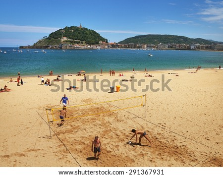 SAN SEBASTIAN or DONOSTIA, SPAIN-JUN 14: San Sebastian or Donostia is a coastal city and located on the coast of the Bay of Biscay. View to the coast, men play beach volleyball on 14 Jun, 2015, Spain. - stock photo