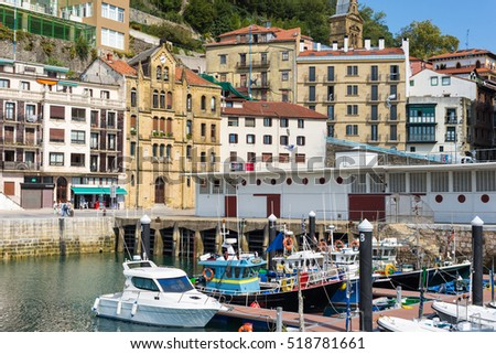 SAN SEBASTIAN, SPAIN  - SEPTEMBER 30. Picturesque houses, fishing boats and sport fishing boats to recreational fishing are moored in the harbor of Donostia San Sebastian September 30, 2016