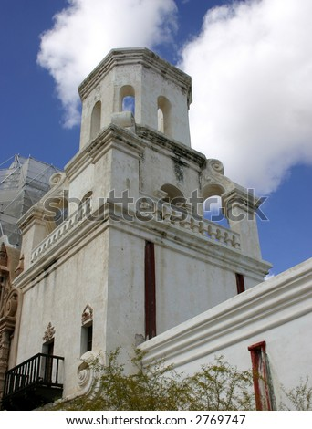 San Xavier del Bac Mission near Tucson Arizona showing bell tower against a blue sky with white cumulus clouds - stock photo