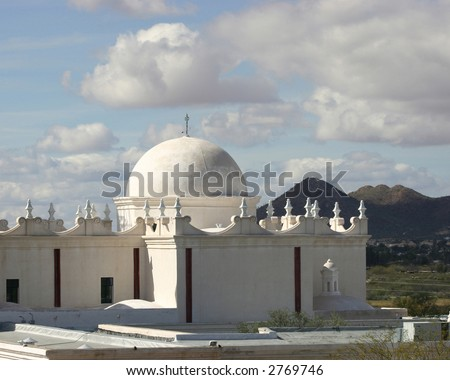 San Xavier del Bac Mission near Tucson Arizona showing dome against a blue sky with white cumulus clouds - stock photo