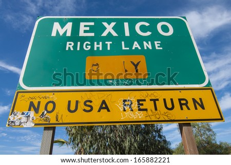 SAN YSIDRO, USA - NOVEMBER 27, 2013: Vandalism covers the traffic sign on the corner of Camino de la Plaza and Interstate 5 on-ramp in San Ysidro that directs drivers to Mexico.