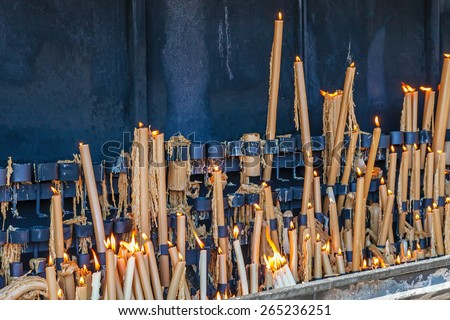 Sanctuary of Fatima, Portugal. Votive candles burning in the pyre as fulfillment of vows made to Our Lady. Fatima is one of the most important pilgrimage locations for Catholics - stock photo