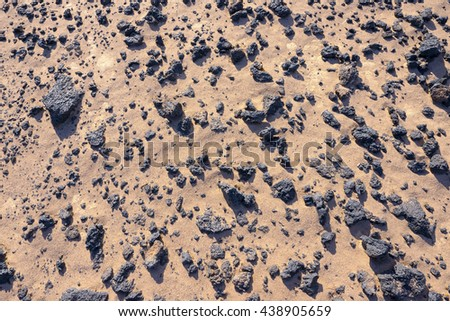Sand and black lava rocks on Mojave Desert - stock photo