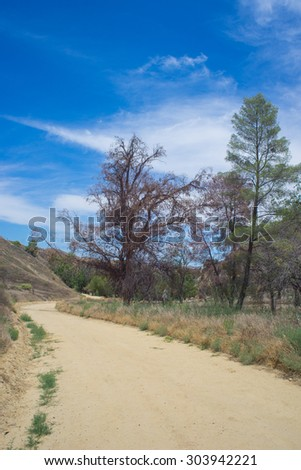 Sand and dirt trail winds through valley in southern California. - stock photo