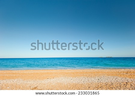 sand-and-pebble beach and a quiet, calm sea - stock photo