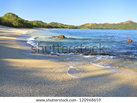 Sand and shells on Playa Conchal and the azure waters of the Pacific Ocean in Guanacaste, Costa RIca - stock photo